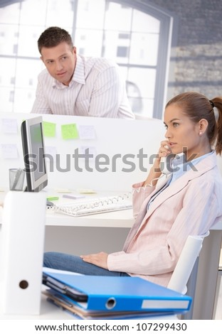 Attractive female office worker chatting on phone in office, male colleague looking at her from background.