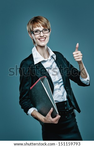 Attractive female office worker holding a folder on blue background