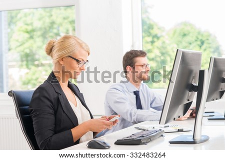 Attractive female office worker in formalwear surfing the smartphone.