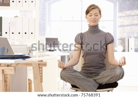 Attractive female office worker practicing yoga, meditating at lotus position. - stock photo