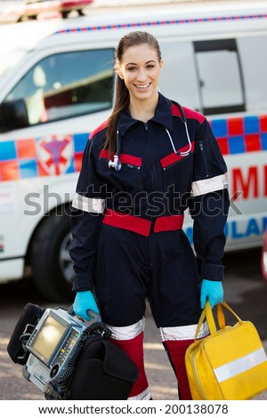 attractive female paramedic holding portable devices - stock photo