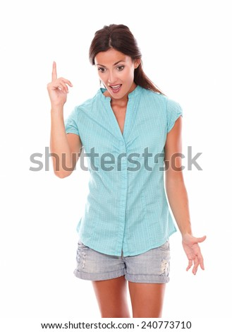 Attractive female pointing up while looking down feeling surprised in white background - copyspace - stock photo