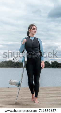 Attractive female posing in a swimsuit with a longboard on a lake, cloudy sky