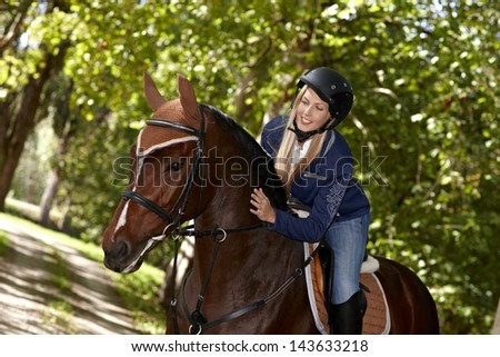 Attractive female rider caressing horse while riding in the woods.
