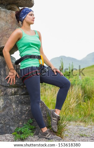 Attractive female rock climber leaning on rock face in the countryside - stock photo