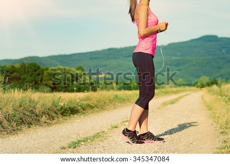 Attractive female runner holding headphones, ready for her workout