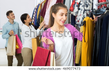 Attractive female shopper chooses liked things in the boutique