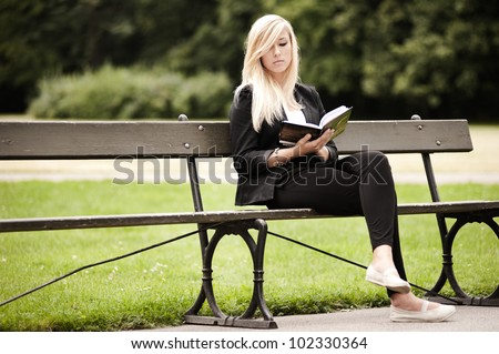 Attractive female sitting in a park with a book - stock photo