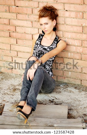 Attractive female sitting next to a brick wall - stock photo