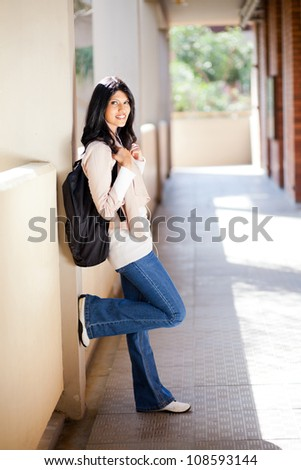 attractive female student standing by university corridor - stock photo