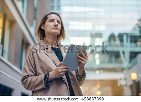 Attractive female student typing on touch screen of tablet near her university, cityscape, Blurred background, flare light, Shallow DOF
