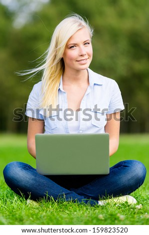 Attractive female student with silver laptop sitting on the green grass in the summer park