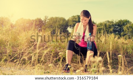 Attractive female taking a break after jogging, holding smartphone and bottle of water