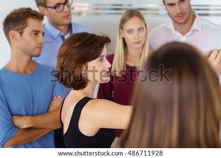 Attractive female team leader brainstorming with a group of serious thoughtful colleagues standing in a group around a flip chart as she writes notes on the paper