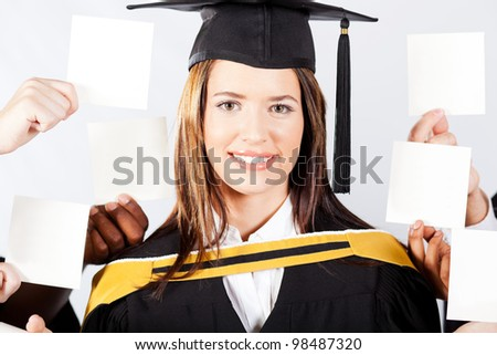 attractive female university graduate with blank notes held around her head - stock photo
