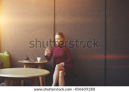 Attractive female watching video or reading business webblog in network on cell telephone, caucasian businesswoman checking e-mail on smart phone while is relaxing during work break in coffee shop  - stock photo