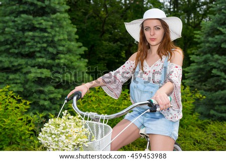 Attractive female wearing a beautiful white hat sitting on her bicycle with a bouquet of little white flowers in a basket in a park - stock photo