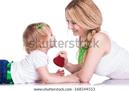 Attractive female with cute baby girl, closeup portrait of young mother and her little daughter holding red heart, studio shot, happy family, child care and love concept. Valentine's Day