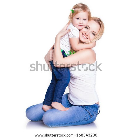Attractive female with cute baby girl, closeup portrait of young mother hug her little daughter, studio shot, happy family, child care and love concept - stock photo