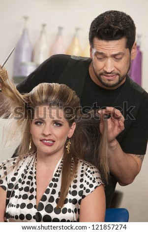 Attractive female with hair problem and embarrassed hair stylist - stock photo