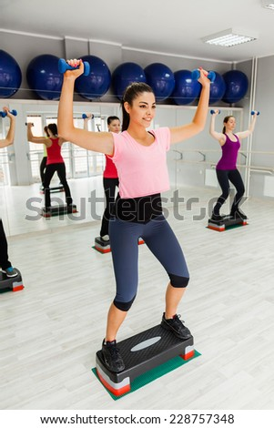 Attractive Females Doing Step Aerobics Exercise With Dumbbells In A Gym - stock photo