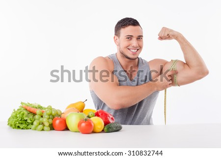 Attractive fit man is flexing his bicep and measuring it with tape-line. He is smiling and sitting at the table near fruits and vegetables. Isolated on background - stock photo