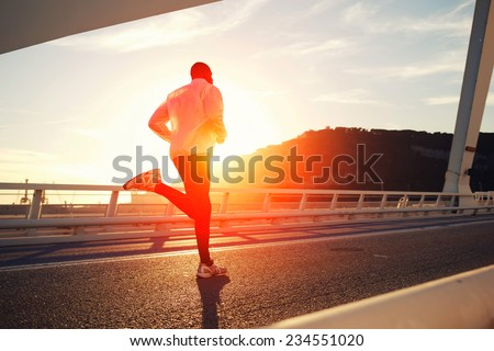 Attractive fit man running fast along big modern bridge at sunset light, black man doing workout outdoors, silhouette runner in windbreaker jogging over bridge road with amazing sunset on background - stock photo