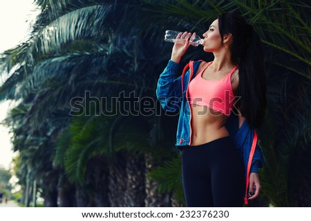 Attractive fit woman dressed in bright sportswear drink water after fitness training outdoors, female runner with perfect body resting after workout refreshing with cold water, fashion sport model - stock photo