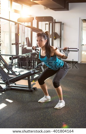Attractive fit woman exercising with weights in gym.