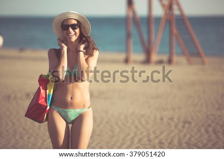 Attractive fit woman in bikini enjoying summer.Going to the beach.Carefree youthful brunette.Summer sandy beach lifestyle and feeling.Having fun.Ready and prepared for summer season - stock photo