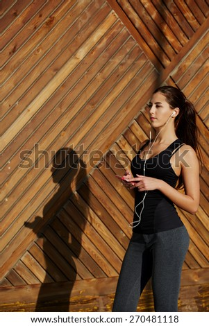 Attractive fit woman in sportswear listening to music with headphones while standing on wooden background with copy space, young female runner enjoying the sun while listen to music though earphones - stock photo