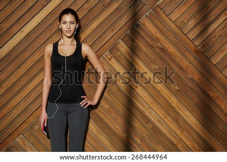 Attractive fit woman in sportswear listening to music with her headphones while standing on wooden background with space, young female runner enjoying the sun while listen to music though earphones - stock photo