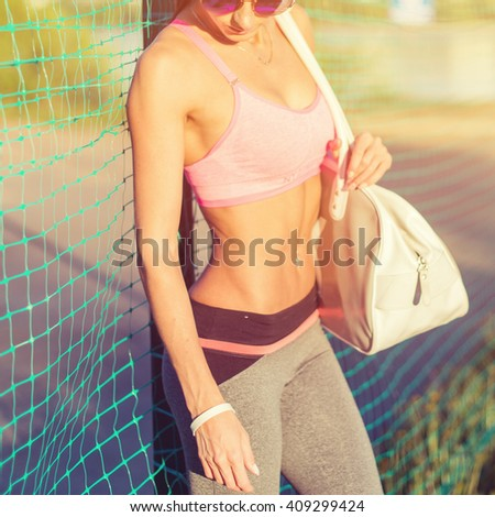 Attractive fit woman in sportswear training outdoors, female athlete with perfect body resting after workout, fashion sport model healthy lifestyle - stock photo
