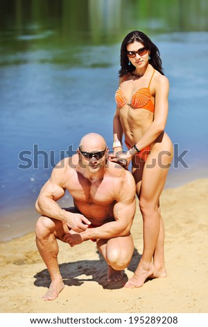 Attractive fitness couple posing on a beach - stock photo