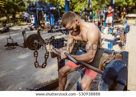 Attractive fitness man doing exercises outdoors. Sport,cross-fit. Training outdoors. Muscular man training outdoors