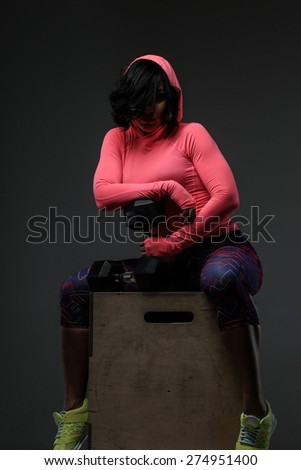Attractive fitness woman in sportswear posing with dumbells in sudio on grey background - stock photo