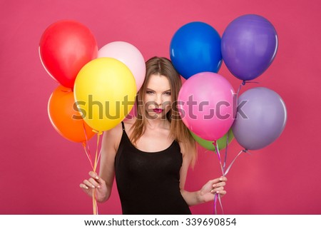 Attractive flirty concentrated young woman with colorful balloons thinking and planning surprise - stock photo