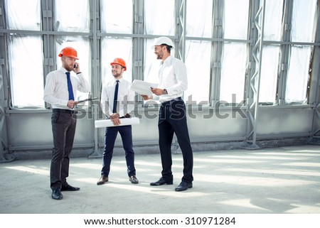 Attractive foreman is talking on the phone with a client seriously. His colleagues are waiting for his answer and smiling. The architect is holding documents in anticipation. Copy space in right side - stock photo