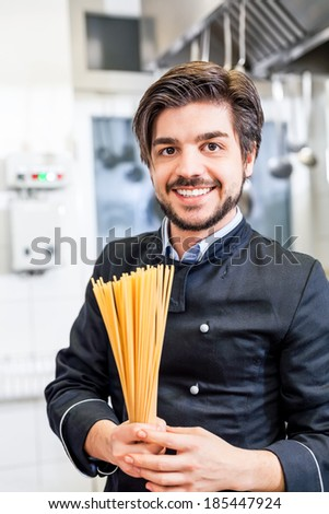 Attractive friendly chef or cook in uniform preparing spaghetti pasta over a gas hob in a commercial kitchen at a hotel or restaurant - stock photo