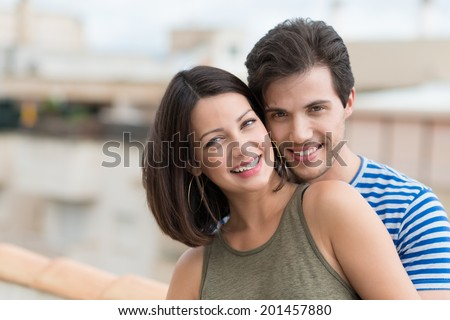 Attractive friendly couple smiling at the camera as they pose with their heads close together outdoors in the sunshine, with copyspace - stock photo