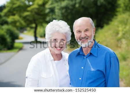 Attractive friendly smiling elderly couple standing side by side in a rural road in the sunshine smiling at the camera - stock photo