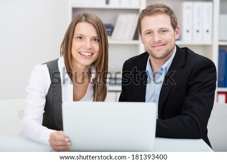Attractive friendly young businessman and woman sitting at a desk together in the office sharing a laptop as they pool their ideas