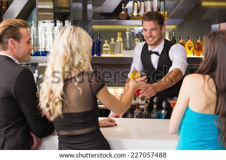 Attractive friends being served cocktails at the bar