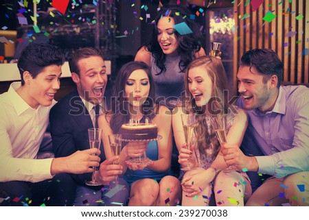 Attractive friends celebrating a birthday against flying colours - stock photo