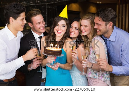 Attractive friends celebrating a birthday at the bar - stock photo