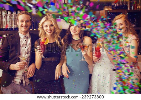 Attractive friends drinking cocktails together against colour curve