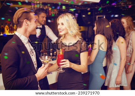Attractive friends drinking cocktails together against flying colours - stock photo
