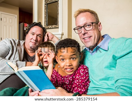 Attractive gay couple reads a book to their children - stock photo