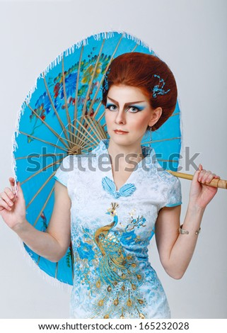Attractive geisha in a smart dress with an umbrella, photographed in the studio - stock photo