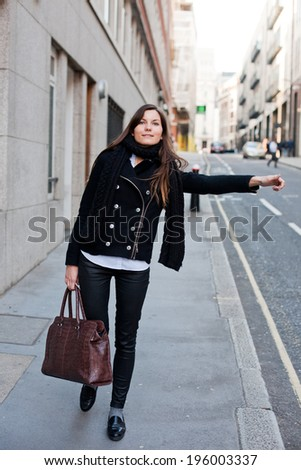 attractive girl catching a taxi on the street, large city